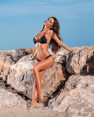 Bonito cuerpo de Heidi con unas rocas sobre la arena de la playa